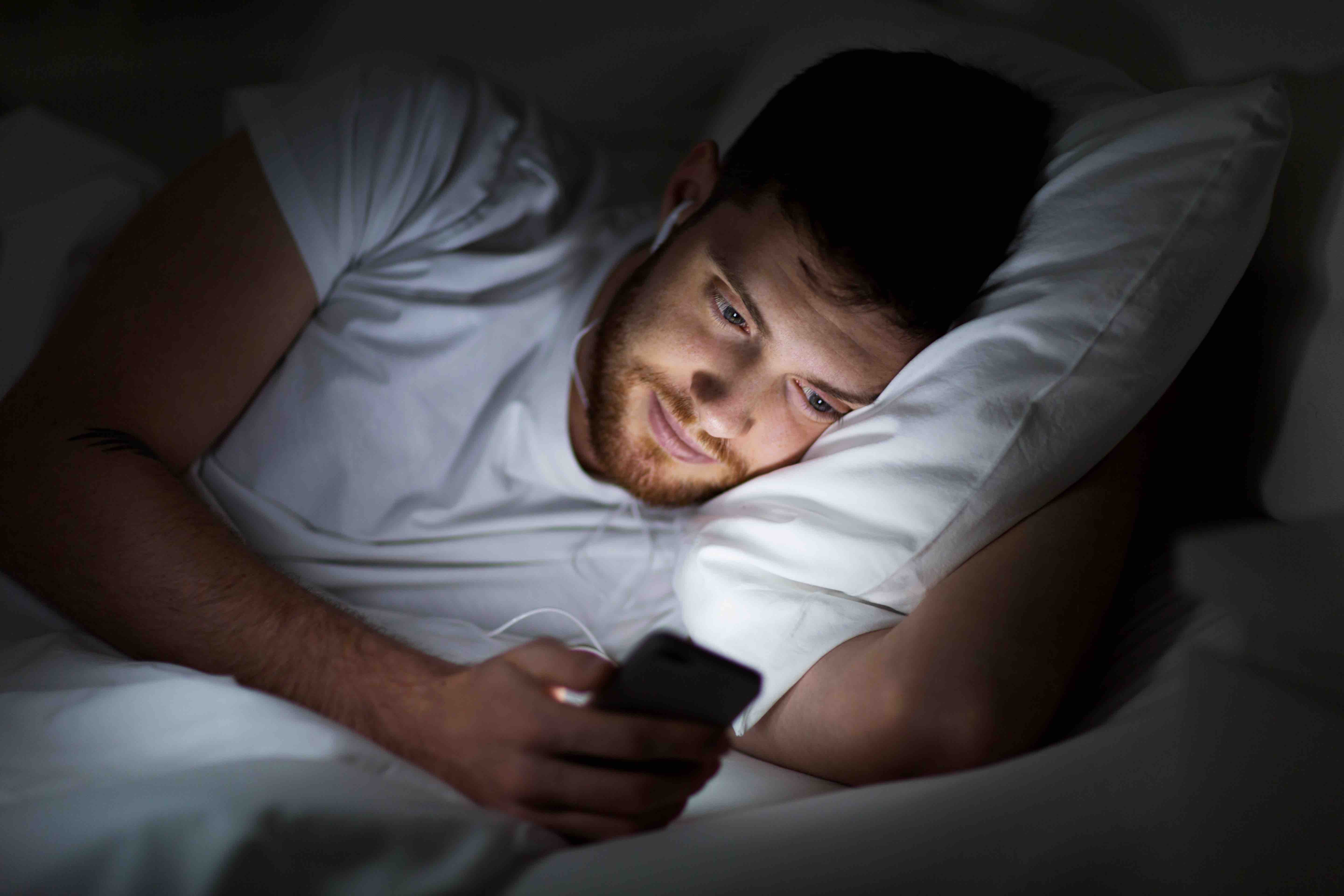 Man with mobile phone in bed